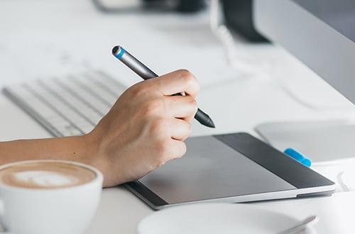Main qui tient un stylo et travaille sur tablette graphique